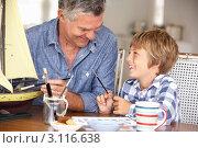 Купить «Седой мужчина с внуком увлеченно клеят модель парусника», фото № 3116638, снято 2 марта 2011 г. (c) Monkey Business Images / Фотобанк Лори