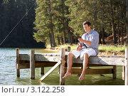 Купить «Мужчина рыбачит с причала на фоне леса», фото № 3122258, снято 22 февраля 2011 г. (c) Monkey Business Images / Фотобанк Лори
