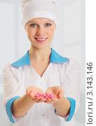Купить «Красивая медсестра с горсткой таблеток в  руке», фото № 3143146, снято 3 января 2012 г. (c) Евгений Атаманенко / Фотобанк Лори