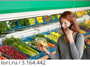 Рыжеволосая молодая женщина разговаривает по телефону в супермаркете, покупает фруктовый салат. Стоковое фото, фотограф CandyBox Images / Фотобанк Лори