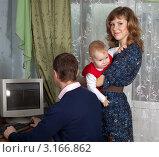Купить «Мужчина работает за компьютером, жена с ребенком на руках стоит рядом», фото № 3166862, снято 15 января 2012 г. (c) Яков Филимонов / Фотобанк Лори