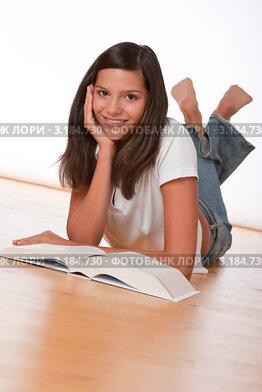 Купить «Улыбающаяся девушка подросток лежит на полу перед книгой», фото № 3184730, снято 9 сентября 2009 г. (c) CandyBox Images / Фотобанк Лори
