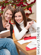 Купить «Радостные молодые подружки подписывают поздравительные открытки на фоне новогодней елки», фото № 3194078, снято 3 октября 2009 г. (c) CandyBox Images / Фотобанк Лори