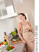 Купить «Улыбающаяся девушка в фартуке на кухне держит бокал вина», фото № 3197050, снято 21 октября 2009 г. (c) CandyBox Images / Фотобанк Лори