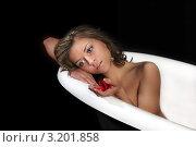 Молодая брюнетка лежит в пустой белой ванной и держит в руке лепестки розы, на черном фоне. Стоковое фото, фотограф Елена Сикорская / Фотобанк Лори