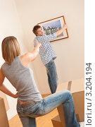 Купить «Парень с девушкой определяют место, куда вешать картину», фото № 3204194, снято 25 ноября 2009 г. (c) CandyBox Images / Фотобанк Лори