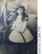 Шестилетняя девочка с длинными волосами стоит с обручем для игры в серсо в 1899 году. Стоковое фото, фотограф Татьяна Беликова / Фотобанк Лори