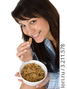 Улыбающаяся темноволосая девушка ест цельнозерновые хлопья. Стоковое фото, фотограф CandyBox Images / Фотобанк Лори