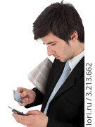 Бизнесмен держит мобильный телефон и кредитную карту. Стоковое фото, фотограф CandyBox Images / Фотобанк Лори