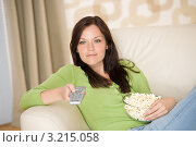 Купить «Девушка в зеленой кофте с попкорном в чаше переключает каналы пультом», фото № 3215058, снято 16 мая 2010 г. (c) CandyBox Images / Фотобанк Лори