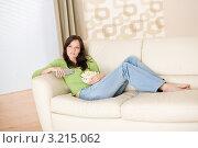 Купить «Шатенка дома на диване  с пультом и попкорном», фото № 3215062, снято 16 мая 2010 г. (c) CandyBox Images / Фотобанк Лори