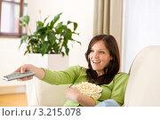 Купить «Счастливая шатенка с телевизионным пультом и попкорном», фото № 3215078, снято 16 мая 2010 г. (c) CandyBox Images / Фотобанк Лори