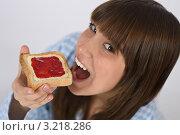 Купить «Портрет молодой брюнетки крупным планом, ест тосты с джемом на завтрак», фото № 3218286, снято 10 марта 2010 г. (c) CandyBox Images / Фотобанк Лори