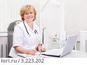 Купить «Улыбающаяся женщина врач в кабинете за столом с ноутбуком», фото № 3223202, снято 11 октября 2011 г. (c) Raev Denis / Фотобанк Лори