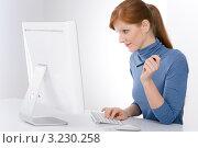 Девушка в синей водолазке в светлом офисе работает за компьютером, глядя в монитор. Стоковое фото, фотограф CandyBox Images / Фотобанк Лори