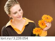 Купить «Симпатичная девушка в коричневой кофте держит в руках три подсолнуха», фото № 3239054, снято 23 февраля 2011 г. (c) CandyBox Images / Фотобанк Лори