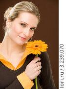Купить «Красивая молодая женщина держит в руках подсолнух», фото № 3239070, снято 23 февраля 2011 г. (c) CandyBox Images / Фотобанк Лори