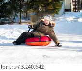 Купить «Радостный мальчик съезжает с высокой горы на тюбинге», эксклюзивное фото № 3240642, снято 29 января 2012 г. (c) Игорь Низов / Фотобанк Лори