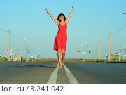 Купить «Девушка в красном платье, с поднятыми вверх руками идет по разделительной полосе», фото № 3241042, снято 21 августа 2018 г. (c) Курганов Александр / Фотобанк Лори