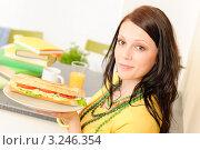 Купить «Растрепанная длинноволосая девушка держит большой бутерброд», фото № 3246354, снято 19 апреля 2011 г. (c) CandyBox Images / Фотобанк Лори