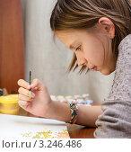 Купить «Девочка склонившись над рисунком с кисточкой смотрит на рисунок», эксклюзивное фото № 3246486, снято 3 февраля 2012 г. (c) Игорь Низов / Фотобанк Лори