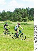 Купить «Молодые мужчина и женщина катаются на велосипедах на свежем воздухе летним днем», фото № 3249330, снято 7 июня 2011 г. (c) CandyBox Images / Фотобанк Лори