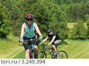 Купить «Портрет счастливой молодой женщины на велосипеде на фоне мужчины», фото № 3249394, снято 7 июня 2011 г. (c) CandyBox Images / Фотобанк Лори