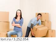 Купить «Девушка отдыхает, а молодой человек поднимает картонную коробку», фото № 3252054, снято 10 августа 2011 г. (c) CandyBox Images / Фотобанк Лори