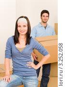 Купить «Девушка отдыхает, а молодой человек поднимает картонную коробку (крупный план)», фото № 3252058, снято 10 августа 2011 г. (c) CandyBox Images / Фотобанк Лори