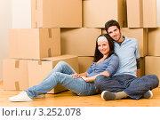 Купить «Уставшие парень и девушка отдыхают на полу на фоне картонных коробок», фото № 3252078, снято 10 августа 2011 г. (c) CandyBox Images / Фотобанк Лори