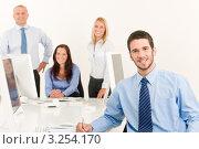 Купить «Деловой брюнет с ручкой в руке за офисным столом, его коллеги на заднем плане», фото № 3254170, снято 27 августа 2011 г. (c) CandyBox Images / Фотобанк Лори