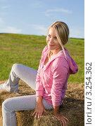 Купить «Девушка греется в лучах заходящего солнца, сидя на стоге сена», фото № 3254362, снято 6 сентября 2011 г. (c) CandyBox Images / Фотобанк Лори