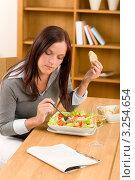 Молодая женщина ест овощной салат на кухне. Стоковое фото, фотограф CandyBox Images / Фотобанк Лори