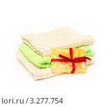 Махровые полотенца и подарочный кусочек мыла, перевязанный красной лентой на белом фоне. Стоковое фото, фотограф Григорий Иваньков / Фотобанк Лори