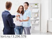 Купить «Менеджер по продаже квартир протягивает ключи от новой квартиры молодой супружеской паре», фото № 3296578, снято 6 октября 2011 г. (c) Raev Denis / Фотобанк Лори