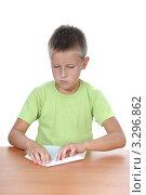 Мальчик складывает листок бумаги сидя за столом. Стоковое фото, фотограф Анфимов Леонид / Фотобанк Лори
