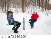 Купить «Старшая и младшая сестра  качаются на качелях зимой», эксклюзивное фото № 3316206, снято 26 февраля 2012 г. (c) Игорь Низов / Фотобанк Лори