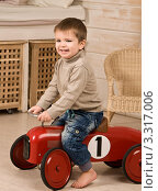 Мальчик катается на маленькой машинке. Стоковое фото, фотограф Сергей Высоцкий / Фотобанк Лори