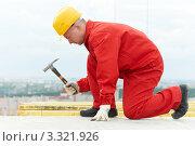 Купить «Рабочий в красной спецовке забивает гвозди», фото № 3321926, снято 15 сентября 2011 г. (c) Дмитрий Калиновский / Фотобанк Лори