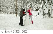 Пара лепит снеговика в лесу. Стоковое видео, видеограф Владимир Никулин / Фотобанк Лори