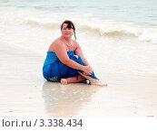 Полная женщина в синем платье сидит на пляже, фото № 3338434, снято 13 января 2012 г. (c) Liseykina / Фотобанк Лори