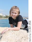 Улыбающаяся девочка на камне на фоне моря, Кипр. Стоковое фото, фотограф Павел Михеев / Фотобанк Лори