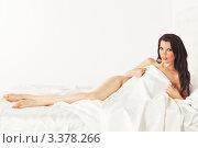 Молодая обнаженная девушка брюнетка лежит в белой постели. Стоковое фото, фотограф Симон Герреро Ушаков / Фотобанк Лори