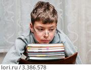 Купить «Задумчивый мальчик сидит на стуле  со стопкой книг», эксклюзивное фото № 3386578, снято 23 марта 2012 г. (c) Игорь Низов / Фотобанк Лори