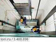 Купить «Два механика монтируют лифт», фото № 3400898, снято 19 марта 2012 г. (c) Дмитрий Калиновский / Фотобанк Лори