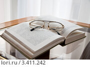Книга и очки, лежащие на столе (2012 год). Редакционное фото, фотограф Артеменко Арина / Фотобанк Лори