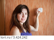 Купить «Женщина включает свет выключателем на стене», фото № 3424242, снято 25 марта 2012 г. (c) Яков Филимонов / Фотобанк Лори
