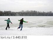 Молодые люди бегут к замерзшему пруду (2012 год). Редакционное фото, фотограф Наталия Журова / Фотобанк Лори