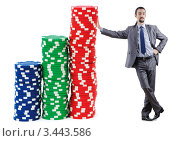Купить «Бизнесмен стоит, опираясь на стопку фишек казино», фото № 3443586, снято 6 января 2012 г. (c) Elnur / Фотобанк Лори