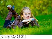Красивая молодая девушка лежит на зеленом лугу. Стоковое фото, фотограф Владимир Логутенко / Фотобанк Лори